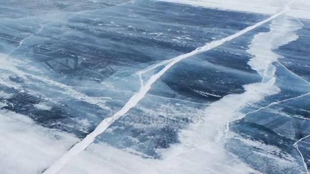 Vítr foukat sněhové vločky na zamrzlé vodní hladině v jezeře Bajkal