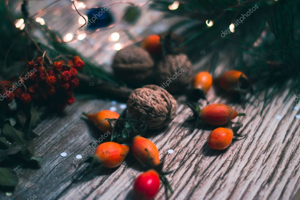 Berries and nuts on wooden boards with a blurred background.