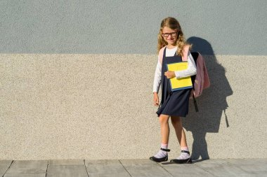Schoolgirl with notebooks in hand.