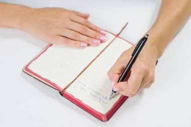 Hand writing in open notebook on table