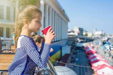 Portrait of a cool girl 10 years old, in profile, drinks from a
