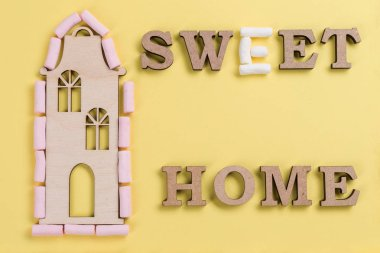 Word sweet home of marshmallow and abstract wooden letters.