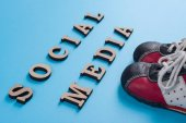 Text social media abstract wooden letters. Blue background with baby sneakers.