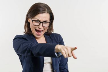 Angry mature business woman screaming, white studio background