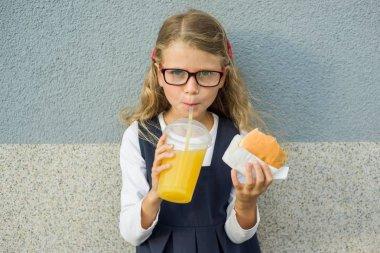 Cute smiling little schoolgirl holding a hamburger and orange juice outdoor