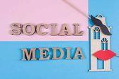 Text-social-Media abstrakte Holzbuchstaben. Blauer Hintergrund mit dem Bild des Hauses und paar Freunde.