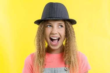 Delight, happiness, joy, victory, success and luck. Teen girl on a yellow background.