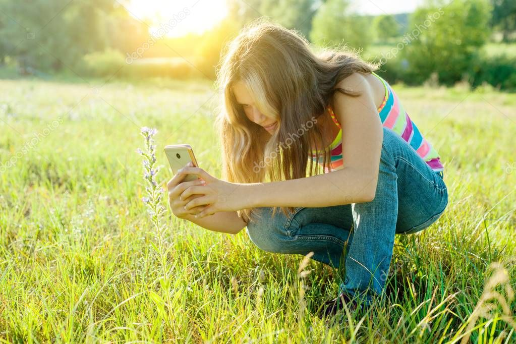Outdoor portrait of a young teenager girl using smartphone for her blog, and pages in social networks.