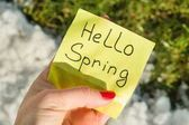 Ahoj jaro. Ženská ruka drží nálepka s ručně psaný text na pozadí tajícího sněhu a zelené trávy