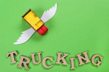 Abstract picture of a truck with wings and a word of trucking. Green background