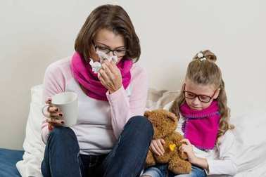 Flu season, sick mother and child at home