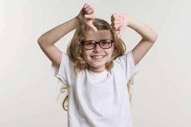 Girl child shows thumb down sign bad, dislike, negative. On white background in white base T-shirt