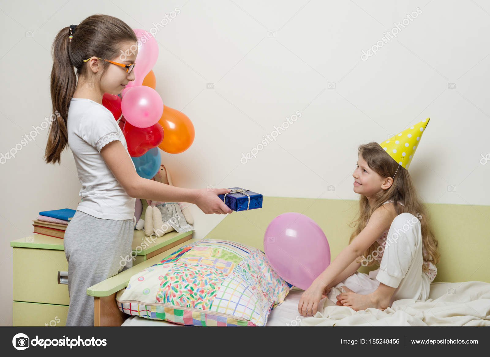Birthday morning. Older sister giving surprise gift to her cute ...