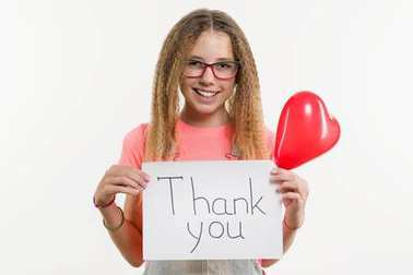 Teenage girl holding a paper with text thank you, heart balloon, white studio background