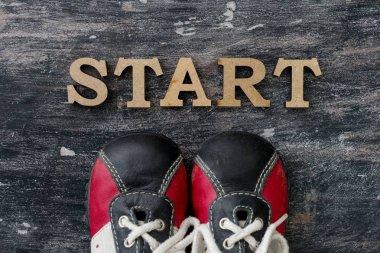 Sneakers before the word start. Dark background