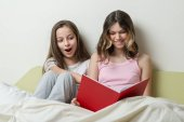 A pizsama két tizenéves lány az ágyban otthon ülni, és nézni a könyvet.