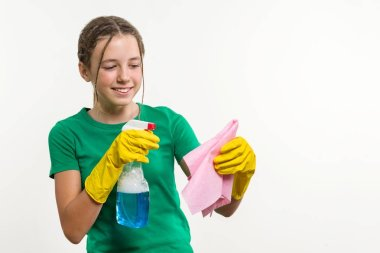 Cleaning day, spring cleanup, housework concept. Girl teenager in yellow gloves with rag and spray detergent.