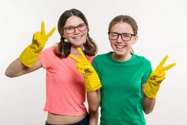 Girls teenagers wearing yellow protective gloves show victory.