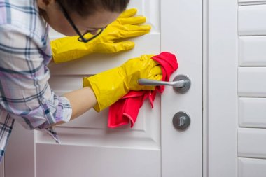 Professional cleaning service. Woman housekeeper wipes the door with rag