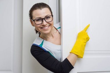 Professional cleaning service. Woman housemaid in yellow rubber gloves pointing with a finger to the white door is the place of copy space