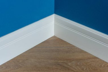 Moulding in the corner. Blue Matte Wall with laminate immitating oak texture