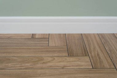 Interior concept. Light matte wall, white baseboard and tiles immitating hardwood flooring
