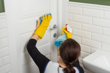Professional cleaning service. Woman housekeeper wipes the door