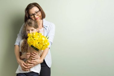 Child congratulates mother and gives her bouquet