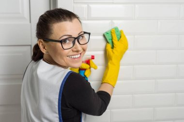 Portrait of cleaning service worker wearing protective rubber gloves, holding sponge and detergent, copy space