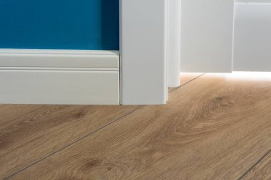 Details in the interior. Laminated parquet floors immitating oak texture, white baseboard, white door.