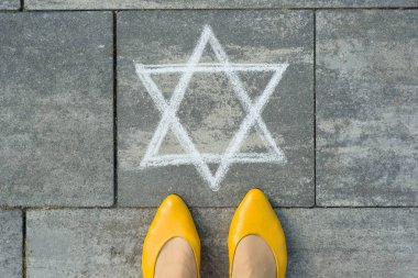 Female feet with abstract image of a six-pointed star, written on grey sidewalk