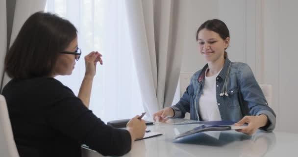 Žena profesionální psychoterapeut, psycholog mluvit s dospívající dívka v kanceláři