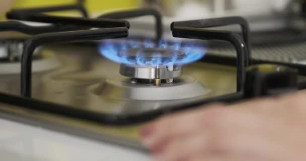 Ženská ruka vypnutí ohně na plynovém hořáku na sporáku v kuchyni, detailní záběr hořáku