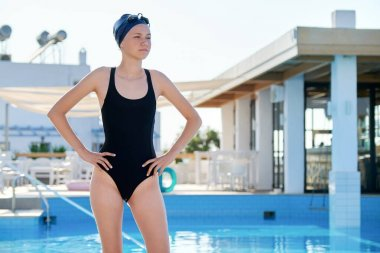 Portrait of girl in swimsuit with goggles swimming cap, outdoor pool