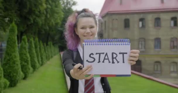 Teenager lány iskolai egyenruhában hátizsák írás és bemutató szó start