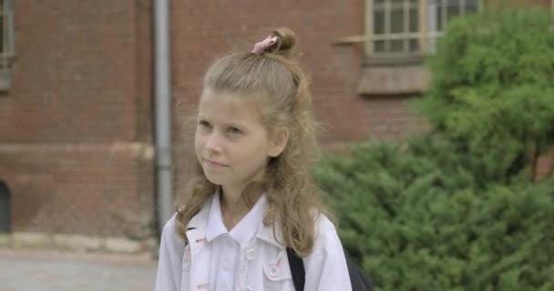 Dívka základní škola student s batohem chůze v blízkosti školní budovy