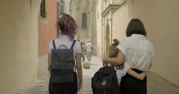Anya és két lánya együtt sétálnak, visszapillantás