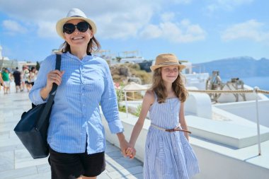 Mother walking with daughter child holding hand in famous tourist village Oia Santorini island. Happy woman and girl on sunny summer day walking together, copy space