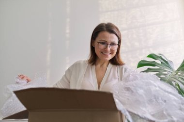 Mature woman unpacks cardboard box on table at home, in office
