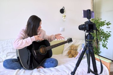 Teenager girl sitting at home on bed with an acoustic guitar, girl playing the guitar recording video on camera. Technology, social networks, art, hobby, teens concept