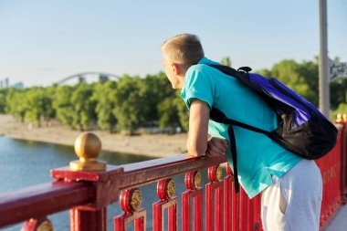 Outdoor portrait of handsome teenager boy 15, 16 years old, with copy space. Guy blond with backpack looks at the river, standing on bridge, sunset sunny summer day, urban lifestyle