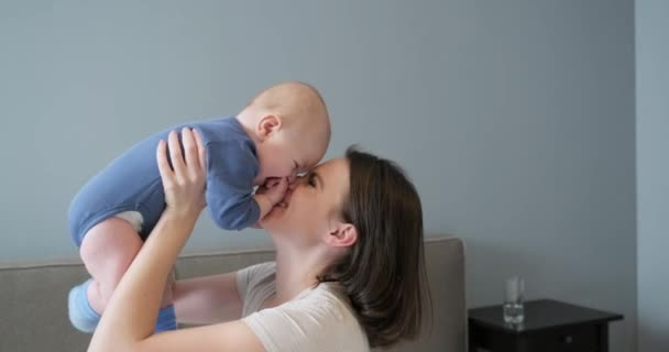 Happy laughing mother and baby, infant boy in arms of young beautiful mother