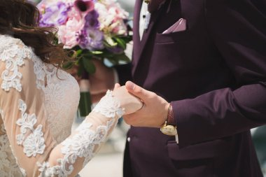 Close- up of the grooms hand holding the bride. Bouquet of flowers.