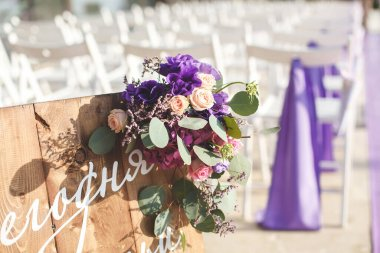 Wedding ceremony, purple flowers, white chairs on the street.