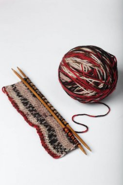 Incomplete knitting project with ball of wool.