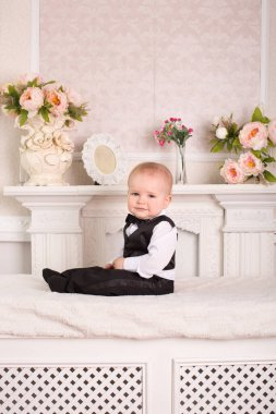 Child in a tuxedo, sitting on the bed next to the fireplace. The groom.