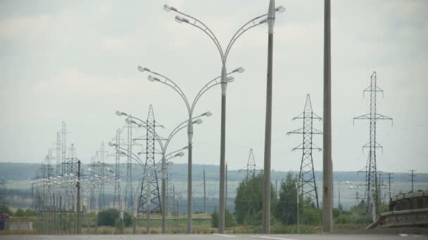 High voltage lines and street lights stand in green field against hilly landscape and grey sky