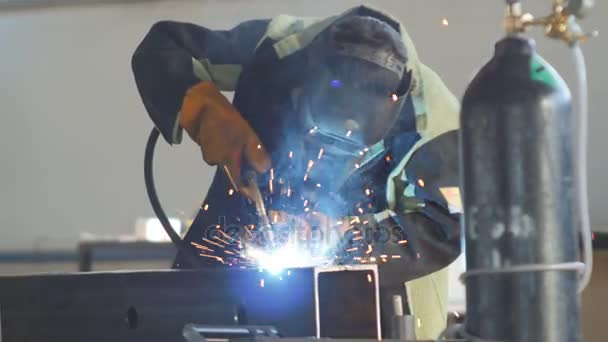 svářeč v masce a ochranný oblek v továrně