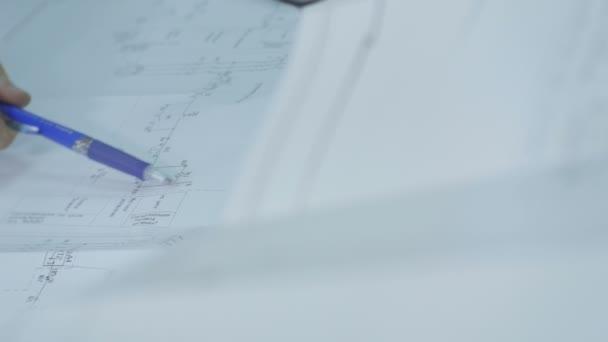 zaměstnanec, zobrazující schémata a výpočty na papír