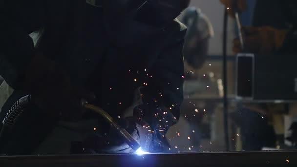 svářeče pracující s svařovací stroje v dílně